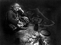 0116618 © Granger - Historical Picture ArchiveNAVAJO AT HOME, c1915.   A Navajo Native American seated on the floor near a fire. Photograph, c1915.