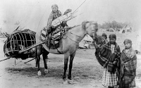 0183936 © Granger - Historical Picture ArchiveCHEYENNE FAMILY, 1889.   The family of Stump Horn, a Northern Cheyenne scout: A girl on horseback holds an infant in a cradleboard, while the horse pulls a travois with two children inside, and three other girls stand nearby. Photographed at Fort Keogh, Montana, 1889, by Christian Barthelmess.
