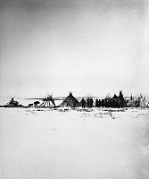 0173224 © Granger - Historical Picture ArchiveCANADA: NASKAPI CAMP, 1882.   A group of Naskapi Native Americans standing next to tipis at a camp in Labrador, Canada, with a cache of furs and hides. Photographed by Lucien M. Turner, 1882.