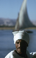 0131926 © Granger - Historical Picture ArchiveEGYPTIAN MAN, c1975.   An Egyptian man traveling on the Nile River, with a felucca seen in the distance. Photographed c1975.