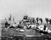0183829 © Granger - Historical Picture ArchiveCOWBOY CAMP, 1898.   A group of cowboys eating beside the Irwin Brothers' chuckwagon near Ashland, Kansas. Photographed by Francis Marion Steele, 1898.