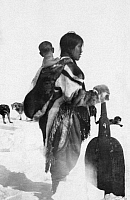 0121206 © Granger - Historical Picture ArchiveCANADA: ESKIMOS.   A Netselingmeut woman holding a snow shovel with a child on her back on the Boothia Peninsula, Nunavut, Canada. Photograph, early 20th century.