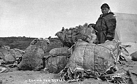 0121526 © Granger - Historical Picture ArchiveALASKA: FUR DEALER.   An Eskimo fur dealer standing next to several bundles of animal hides, Nome, Alaska. Photographed by the Lomen Brothers, early 20th century.