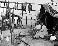 0121535 © Granger - Historical Picture ArchiveALASKA: ESKIMOS, c1916.   Two Eskimo women sitting outside their tent, with fish hanging to dry above them, Nome, Alaska. Photograph, c1916.