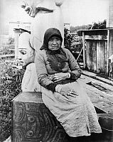 0121563 © Granger - Historical Picture ArchiveALASKA: ESKIMO WOMAN.   A seated Eskimo woman with totem pole sculptures behind her, Auk-Si-Eager, Fort Wrangle, Alaska. Photographed by Frank H. Nowell, c1904.