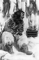 0121990 © Granger - Historical Picture ArchiveESKIMO AND PHONOGRAPH.   An Eskimo man sitting among furs listening to the phonograph, probably originally photographed during the filming of Robert J. Flaherty's 1922 movie 'Nanook of the North.' Photograph by Robert Joseph Flaherty, c1922.