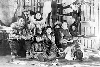 0122034 © Granger - Historical Picture ArchiveALASKA: ESKIMO FAMILY.   An Eskimo family wearing traditional fur clothing, seated inside their home made of logs, Alaska. Photographed by Frank E. Kleinschmidt, November 1924.
