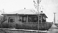 0124389 © Granger - Historical Picture ArchiveALASKA: LOG CABIN.   A log cabin on a residential corner with a wooden plank sidewalk in Fairbanks, Alaska. Photograph, c1900-1916.