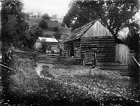 0124407 © Granger - Historical Picture ArchiveOHIO: LOG CABIN, c1909.   An old couple in a horse-drawn carriage beside a log farm building, Ohio. Photograph, c1909.
