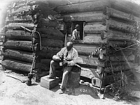 0124570 © Granger - Historical Picture ArchiveLOG CABIN, c1895.   An African American man seated on a tree stump, outside a log cabin in rural America while pouring a drink into cup with a young girl seated in the window above him. Photograph, c1895.