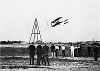 0171746 © Granger - Historical Picture ArchiveEARLY AIRPLANE, 1909.   Men watching the flight of a biplane at Fort Myer, Virginia, 2 July 1909.