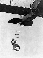 0060709 © Granger - Historical Picture ArchiveAIRPLANE STUNT MAN, 1921.   'Fearless Freddie,' a Hollywood stunt man, clinging to a rope ladder attached to an airplane as he prepares to jump into an automobile below. Photographed in 1921.