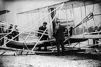 0117901 © Granger - Historical Picture ArchiveWRIGHT AIRPLANE, 1909.   Wilbur Wright examining a canoe attachment before making the first flight around the Statue of Liberty in the Wright Model A Flyer. Photographed on 29 September 1909, New York Harbor, New York.
