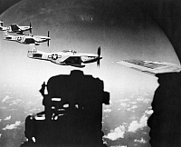 0028716 © Granger - Historical Picture ArchiveB29 SUPERFORTRESS, 1945.  A waist gunner of a B-29 superfortress watches a trio of escorting P-51 Mustangs flying close-in during a fighter sweep to Japan, 1945.