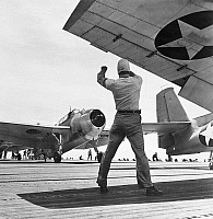 0091725 © Granger - Historical Picture ArchiveTHE FIGHTING LADY, 1944.   A signal officer directs a fighter plane on board the USS Yorktown in a scene from the American propaganda film, 'The Fighting Lady,' 1944.
