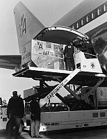 0171774 © Granger - Historical Picture ArchiveAMERICAN AIRLINES CARGO.   Men loading cargo onto a Boeing 747 airplane operated by American Airlines. Photograph, late 20th century.