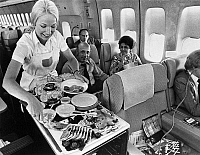 0171810 © Granger - Historical Picture ArchivePAN AMERICAN SERVICE.   A Pan American flight attendant serves a meal to passengers on board. Photograph, c1975.