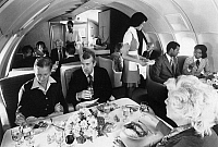 0171831 © Granger - Historical Picture ArchivePAN AMERICAN AIRPLANE.   First-class passengers eating a meal on board a Pan American airplane, 1970s or 1980s.