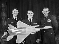 0091503 © Granger - Historical Picture ArchiveAIR FORCE PILOTS, 1975.   U.S. Air Force pilots who set eight time-to-climb records with the F-15 Eagle jet fighter aircraft in climbs from three thousand to thirty thousand meters, 1975. A model of the F-15 is in the foreground. Left to right: Major David Peterson, Major Willard Macfarlane and Major Roger Smith.