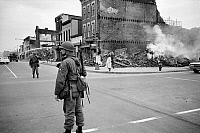 0125837 © Granger - Historical Picture ArchiveWASHINGTON: RIOTS, 1968.   A soldier standing guard in a street in Washington, D.C., across from the ruins of buildings destroyed in the rioting that followed the assassination of Martin Luther King, Jr. Photographed by Warren K. Leffler, 8 April 1968.