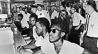 0128469 © Granger - Historical Picture ArchiveLUNCH COUNTER SIT-IN, 1961.   Four young black men sitting in at a segregated lunch counter at a drug store in Jackson, Mississippi, soon to be arrested by police officers (rear) for refusing an order to leave, 13 July 1961.