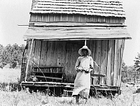 0123135 © Granger - Historical Picture ArchiveSHARECROPPER, 1937.   Sharecropper's wife standing in front of a cabin south of Jackson, Mississippi. Photograph by Dorothea Lange, June 1937.