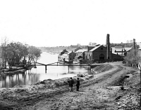 0013323 © Granger - Historical Picture ArchiveCIVIL WAR: FALL OF RICHMOND.   View of the Tredegar Iron Works, with footbridge to Neilson's Island. Photographed in April 1865 by Alexander Gardner.