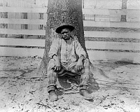 0113199 © Granger - Historical Picture ArchiveGEORGIA: CHAIN GANG.  African American man sitting against a tree with legs chained, Thomasville, Georgia. Photograph, c1890.