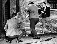 0093003 © Granger - Historical Picture ArchiveDETECTIVE TRAINING, 1955.   An F.B.I. agent (kneeling) gives advice on how to approach an armed criminal to two Philadelphia detectives in training, 1955.