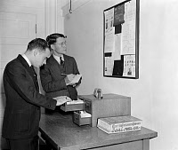 0216691 © Granger - Historical Picture ArchiveSECRET SERVICE AGENTS, 1938.   Agents of the U.S. Secret Service getting the latest criminal news from a bulletin board at Secret Service headquarters in the Treasury Department, Washington, D.C., October 1938.