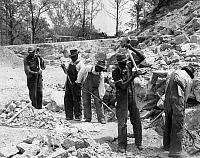 0118948 © Granger - Historical Picture ArchivePRISONERS.   Five African American convicts breaking up rocks for road construction at a prison camp in rural America. Photograph, c1934-1950.