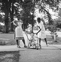 0125519 © Granger - Historical Picture ArchiveMISSISSIPPI: MAIDS, 1940.   Two African American maids caring for a white child, in Port Gibson, Mississippi. Photograph by Marion Post Wolcott, 1940.