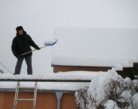 0620338 © Granger - Historical Picture ArchiveGERMANY: WINTER, 2010.  Man shoveling snow from a roof in Brandenburg, Germany. Photograph by Iiona Studre, 29 December 2010. Full Credit: ullstein bild - Ilona Studre / Granger, NYC. All Rights Reserved.