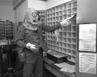 0268396 © Granger - Historical Picture ArchiveFALLOUT DRILL, 1978.   An airman sorting mail while wearing a gasmask during a fallout drill. Photograph, 3 October 1978.