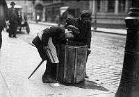 0107064 © Granger - Historical Picture ArchiveSTREET BOYS, 1916.   Three boys looking through a garbage can, Fall River, Massachusetts. Photographed on 16 June 1916 by Lewis Hine.