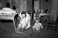 0122205 © Granger - Historical Picture ArchiveSHARECROPPER HOME, 1938.   Sharecropper's wife with her baby and young child inside a shack without windows, Missouri. Photograph by Russell Lee, May 1938.