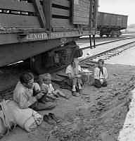 0123106 © Granger - Historical Picture ArchiveHOMELESS FAMILY, 1939.   A destitute farmer with his family seated beside railroad tracks after traveling by freight train to the Yakima Valley, Toppenish, Washington State. Photograph by Dorothea Lange, August 1939.