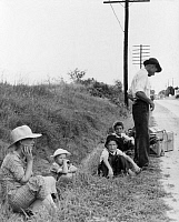 0124298 © Granger - Historical Picture ArchiveMIGRANT FAMILY, 1937.   A family hitchhiking along the highway in Macon, Georgia and heading back to their home state of Alabama where the father can repair sewing machines and lawn mowers without a license. Photograph by Dorothea Lange, July 1937.