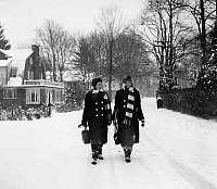 0130183 © Granger - Historical Picture ArchiveNEW YORK: WINTER, 1960s.   Two high school students walking to school on a snowy day in Scarsdale, New York, 1960s.