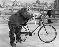0091794 © Granger - Historical Picture ArchiveCIRCUS: CLOWN, c1920.   Clown Joe Jackson, Sr. (né Joseph Francis Jiranek, 1873-1942) with the bicycle used in his act. Photographed c1920.