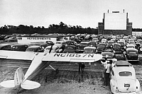 0170362 © Granger - Historical Picture ArchiveDRIVE-IN THEATER, 1951.   A small plane at a drive-in, fly-in theater, where a newsreel is playing, at East Dennis, Massachusetts, where planes land at a nearby airport and taxi down special runways to the theater. Photograph, 1951.