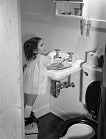 0165671 © Granger - Historical Picture ArchiveGIRL WASHING HANDS, 1942.   Three-year-old Ann Heath, daughter of a Warren McArthur factory lathe operator, standing on a footstool to wash her hands in the bathroom sink at her home, one of the four-room housing units constructed for defense industry employees in Bantam, Connecticut. Photographed by Howard R. Hollem, 1942.