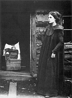0067590 © Granger - Historical Picture ArchiveFRONTIER WOMAN & BABY.   A woman on the Oregon frontier stands outside a cabin while her baby, in a makeshift cradle, sleeps in the doorway. Photograph, 19th century.