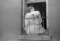 0268350 © Granger - Historical Picture ArchiveEVANS: NEW YORK, 1938.   A woman sitting in window of her apartment on 61st Street between 1st and 3rd Avenues, New York, New York. Photograph by Walker Evans, 1938.