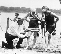 0047455 © Granger - Historical Picture ArchiveBATHING SUITS, 1922.   A Public Buildings and Grounds officer measures women's bathing suits to ensure they are not more than six inches above the knee, Washington, D.C., 1922.