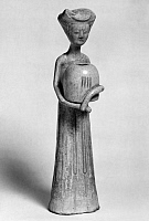 0123377 © Granger - Historical Picture ArchiveCHINA: TOMB FIGURE.   Glazed earthenware tomb figure of a young lady carrying a hand warmer. Height: 10 in. T'ang Dynasty, 7th-8th century.