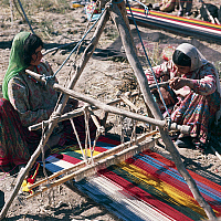 0423398 © Granger - Historical Picture ArchiveDECORATIVE ARTS.   Boyer Ahmadi tribeswomen weaving on horizontal loom, Qashqai people, Zohreh River valley, Fars province, Iran Full credit: De Agostini / N. Cirani / Granger, NYC -- All Rights Reserved.