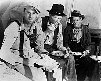 0120920 © Granger - Historical Picture ArchiveGRAPES OF WRATH, 1940.   Henry Fonda, left, as Tom Joad, in the 1940 film version, directed by John Ford, of John Steinbeck's novel 'The Grapes of Wrath.'