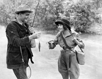 0003807 © Granger - Historical Picture ArchiveSILENT FILM STILL: SPORTS.   Couple going fishing in a scene from a silent film, early 20th century.
