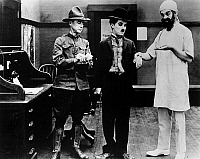 0122887 © Granger - Historical Picture ArchiveCHAPLIN: SHOULDER ARMS.   Charlie Chaplin, center, undergoing a medical examination in his World War I film 'Shoulder Arms,' 1918.